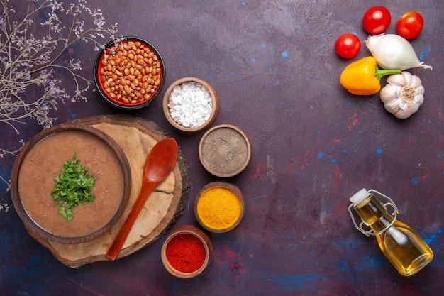 Bovenaanzicht bruine bonensoep heerlijke gekookte soep met verschillende smaakmakers op het donkere oppervlak diner soep maaltijd bonen eten