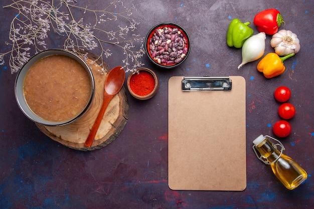 Bovenaanzicht bruine bonensoep met groenten op donkere bureausoep groentemaaltijdvoedsel keukenboon