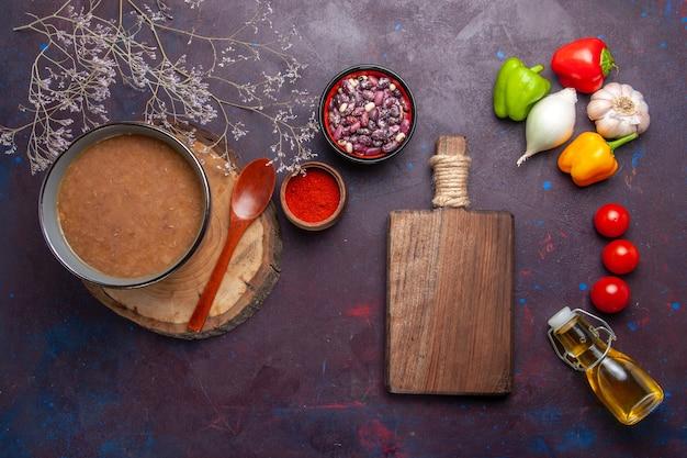Bovenaanzicht bruine bonensoep met groenten op een donkere ondergrond soepgroenten maaltijd voedsel keukenboon