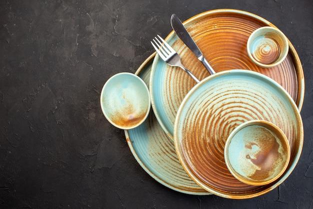 Bovenaanzicht bruine borden met mes en vork op donkere ondergrond