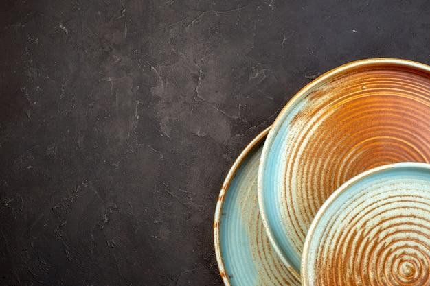 Bovenaanzicht bruine borden op donkere ondergrond