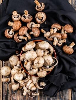 Bovenaanzicht bruine en witte champignons in kom op zwarte doek