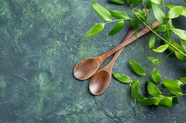 Bovenaanzicht bruine houten lepels op donkerblauwe achtergrond voedsel keuken peper oude maaltijd keuken kruiden