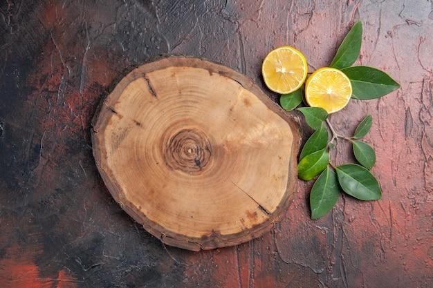 Bovenaanzicht bruine houten tafel met citroen op donker tafelfruit