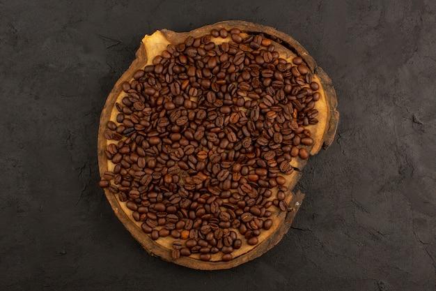 Bovenaanzicht bruine koffie zaden op het bruine bureau en donker