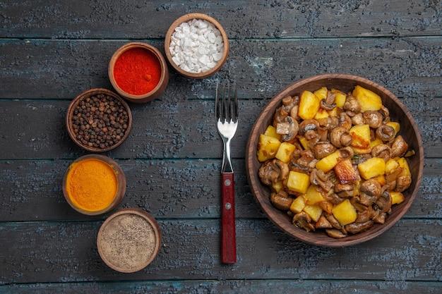 Bovenaanzicht bruine kom met eten een kom aardappelen en champignons naast de vork en verschillende kleurrijke kruiden