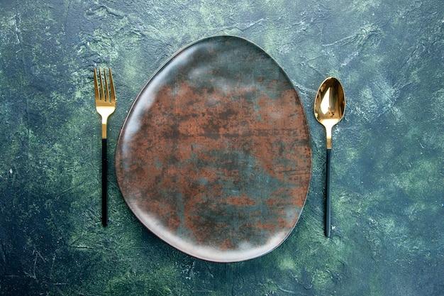 Bovenaanzicht bruine plaat met gouden lepel en vork op donkere achtergrond kleur bestek restaurant eten keuken utencil diner
