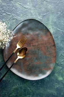 Bovenaanzicht bruine plaat met gouden lepel en vork op donkere ondergrond kleur voedsel restaurant keuken gebruiksvoorwerp diner maaltijd bestek