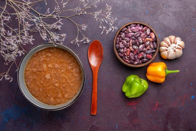 Bovenaanzicht bruine soep in plaat met bonen op het donkere oppervlak soep plantaardige maaltijd voedsel keuken olie Gratis Foto