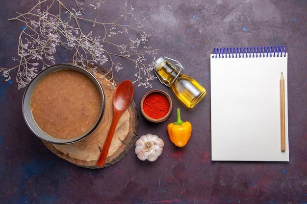 Bovenaanzicht bruine soep met olijfolie blocnote en knoflook op donkere ondergrond soep plantaardige maaltijd voedsel keukenboon