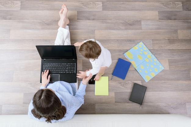 Bovenaanzicht brunette vrouw met laptop en kind zittend op de vloer