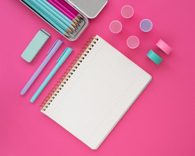 Bovenaanzicht bureau arrangement met roze achtergrond