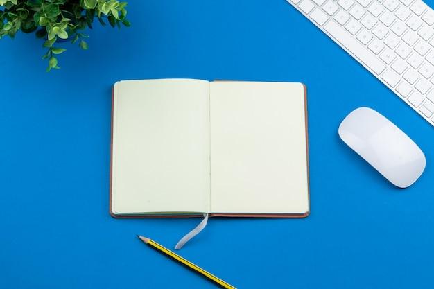 Bovenaanzicht bureau met laptop, notebooks en koffiekopje.