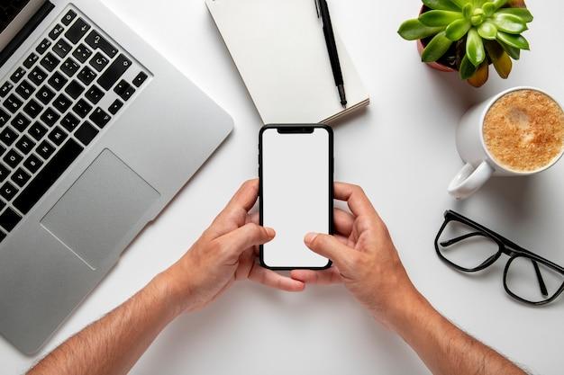 Bovenaanzicht bureau met telefoon in handen