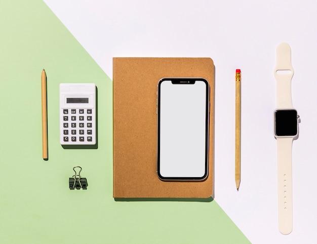 Bovenaanzicht bureau minimaal met accessoires en telefoon