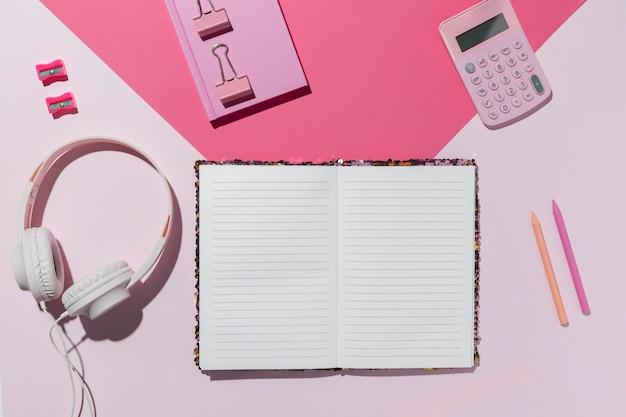 Bovenaanzicht bureau minimaal open notitieboekje en koptelefoon