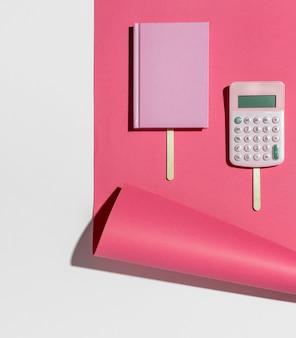Bovenaanzicht bureau minimaal roze notitieboekje en rekenmachine