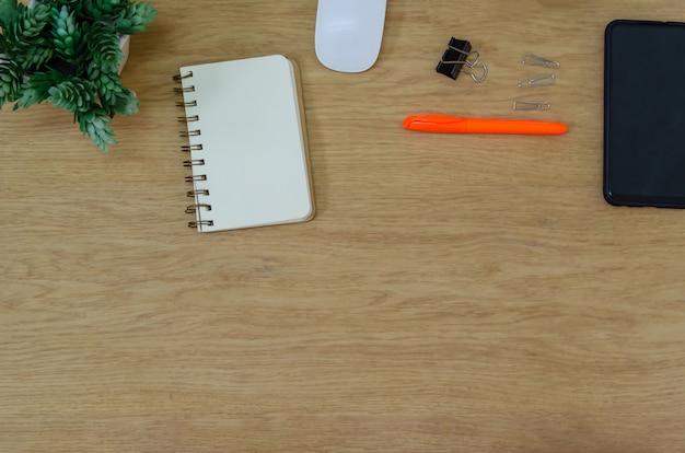 Bovenaanzicht bureau smartphone, muis, bloem, blocnote en pen op houten tafel. plat leggen kopie spce. werk voor thuis