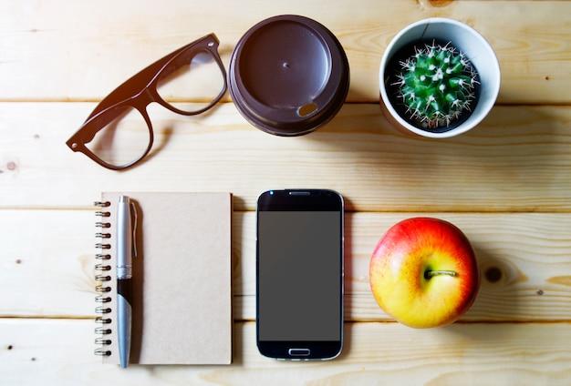 Bovenaanzicht bureau tafel met koffiekopje, smartphone, cactus, glazen, notebook, appel, plat lag.