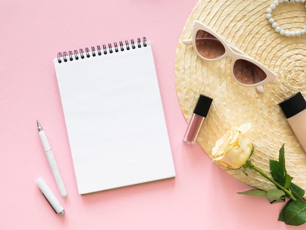 Bovenaanzicht bureau van mode vrouw. notitieboekjemodel, pen en roze bloem over roze achtergrond. kopieer ruimte.