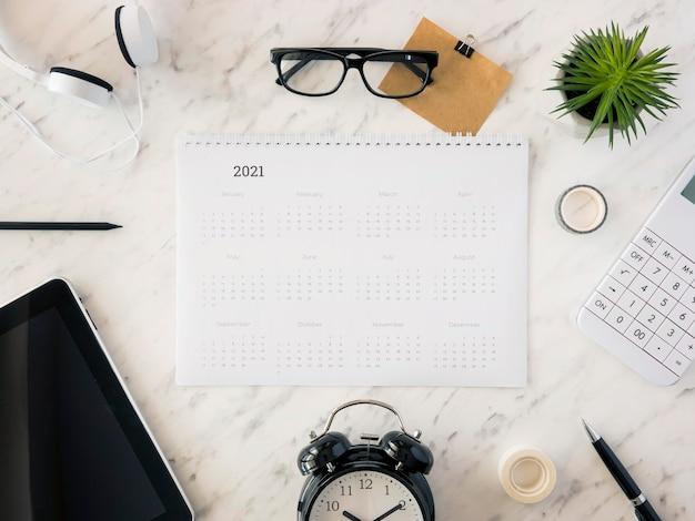 Bovenaanzicht bureaukalender op marmer met accessoires