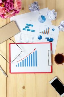 Bovenaanzicht business office de grafieken en grafieken ook notitieboekje, zwarte koffie, bloem, stationaire, pen op kantoor bureau achtergrond.
