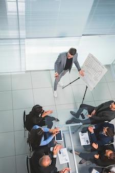 Bovenaanzicht. business team applaudisseren de spreker na de bedrijfspresentatie. succes concept