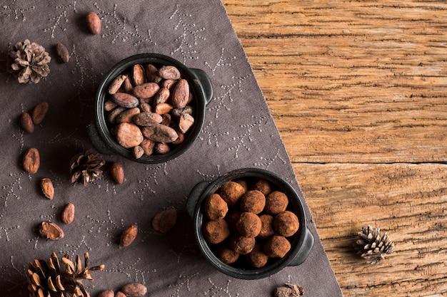 Bovenaanzicht cacaobonen en chocolade truffels in kommen