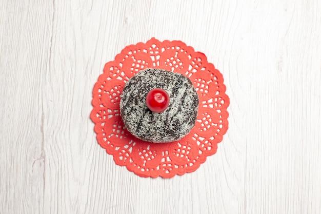 Bovenaanzicht cacaocake met zure kers op het rode ovale kanten kleedje op de witte houten tafel