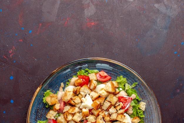 Bovenaanzicht caesar salade met gesneden groenten en beschuit op het donkere bureau groentesalade eten lunch maaltijd beschuit smaak