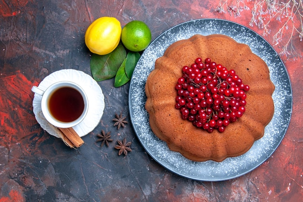 Bovenaanzicht cake cake met bessen limoen citroen een kopje thee steranijs bladeren