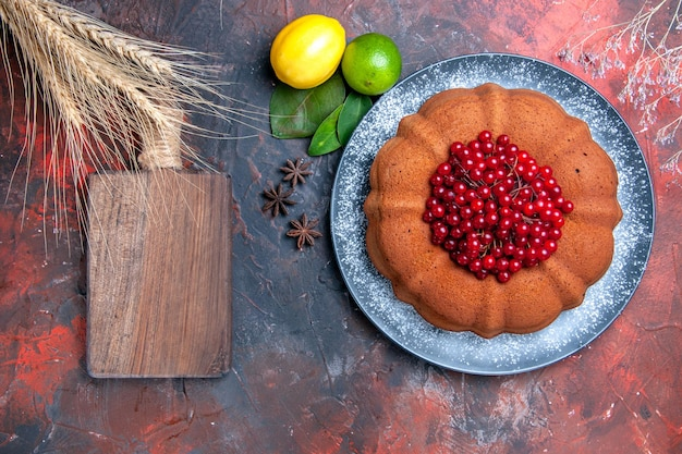 Bovenaanzicht cake citroenen limoenen bladeren steranijs cake met rode aalbessen snijplank