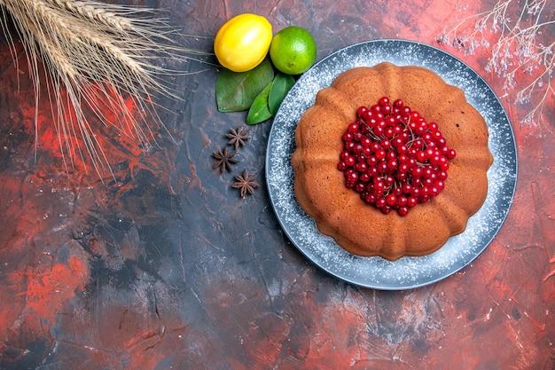 Bovenaanzicht cake citroenen limoenen bladeren steranijs cake met rode aalbessen tarwe oren