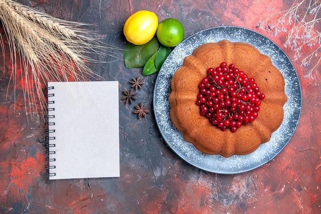 Bovenaanzicht cake citroenen limoenen bladeren steranijs cake met rode aalbessen wit notitieboekje