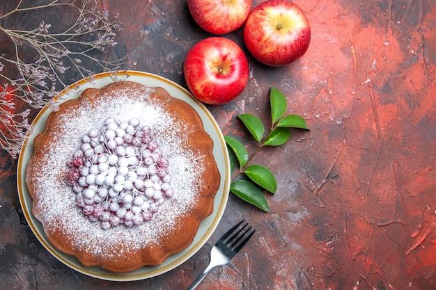 Bovenaanzicht cake een cake met bessen vork appels bladeren takken