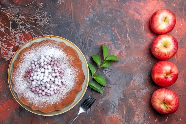 Bovenaanzicht cake een smakelijke cake met bessen vier rode appels vork bladeren