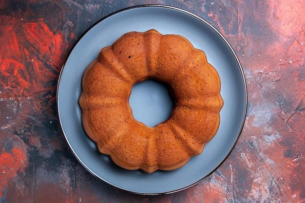 Bovenaanzicht cake een smakelijke cake op de blauwe ronde plaat op de blauwrode tafel