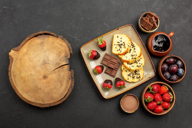 Bovenaanzicht cake en aardbeien smakelijke cake met chocolade en aardbeien en kommen met aardbeien, bessen en chocoladesaus naast de bruine snijplank