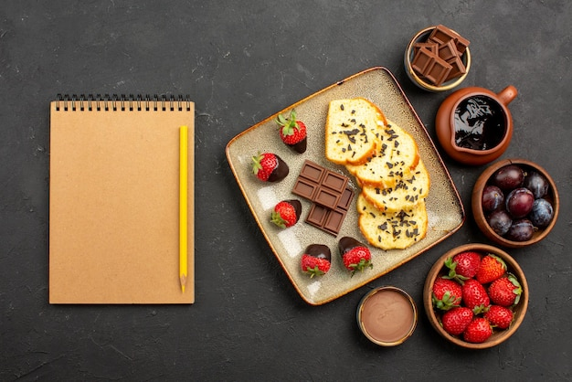 Bovenaanzicht cake en aardbeien smakelijke cake met chocolade en aardbeien en kommen met aardbeien, bessen en chocoladesaus naast roomnotitieboekje en potlood