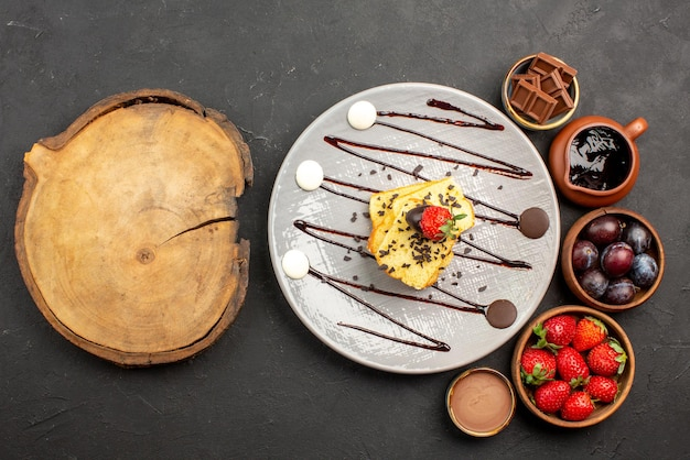 Bovenaanzicht cake met aardbeien aardbeien chocolade en bessen in kommen en bord cake met aardbeien en chocoladesaus naast de snijplank op tafel