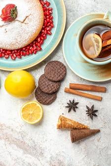 Bovenaanzicht cake met aardbeien kaneel een kopje thee met citroen de cake cookies