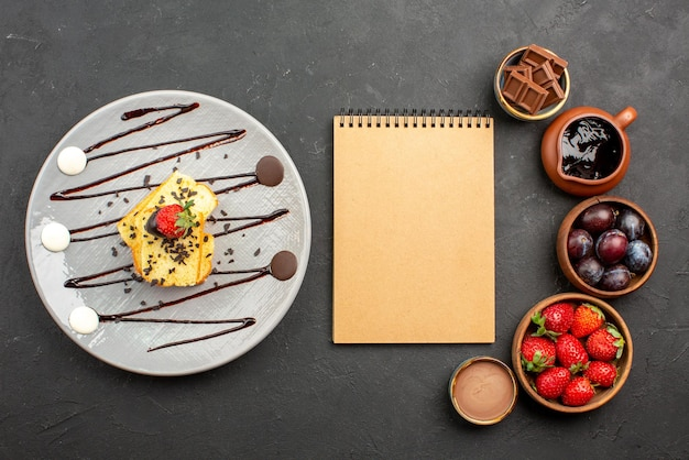 Bovenaanzicht cake met aardbeienroomnotitieboekje tussen aardbeienchocolade in kommen en bord cake met chocoladesaus op het donkere oppervlak