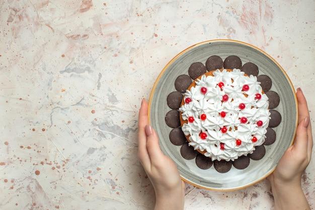 Bovenaanzicht cake met banketbakkersroom en chocolade in vrouwelijke hand