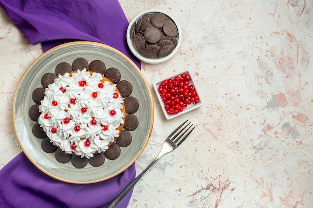 Bovenaanzicht cake met banketbakkersroom en chocolade op bord paarse sjaalkommen met chocolade en bessenvork