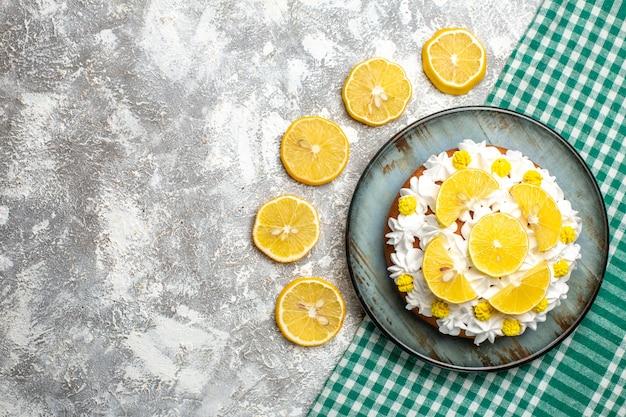 Bovenaanzicht cake met banketbakkersroom en citroen op ronde schotel op groen wit geruit tafelkleed