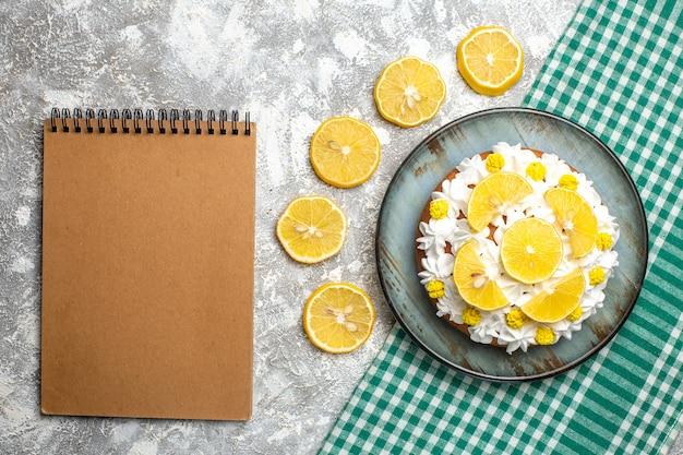 Bovenaanzicht cake met banketbakkersroom en citroen op schotel op groen wit geruit tafelkleed
