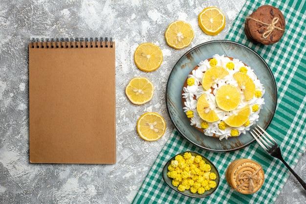 Bovenaanzicht cake met banketbakkersroom en citroenvork op schotel koekjes snoepjes in kom op groen wit geruit tafelkleed. leeg notitieboekje