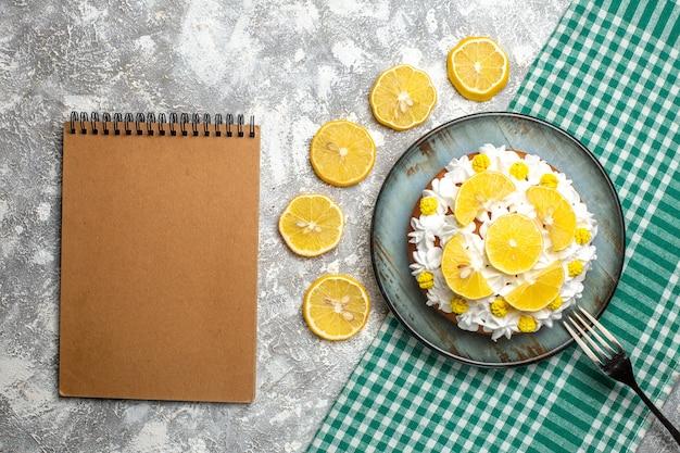 Bovenaanzicht cake met banketbakkersroom en citroenvork op schotel op groen wit geruit tafelkleed. leeg notitieboekje