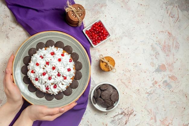 Bovenaanzicht cake met banketbakkersroom op bord in vrouwelijke hand paarse sjaal koekjes vastgebonden met touwbessen in kom