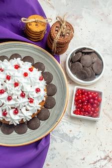 Bovenaanzicht cake met banketbakkersroom op bord paarse sjaalkoekjes vastgebonden met touwchocolade en bessen in kommen op witte tafel